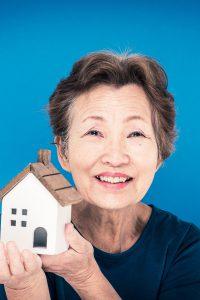 住宅の模型を持っているシニア女性